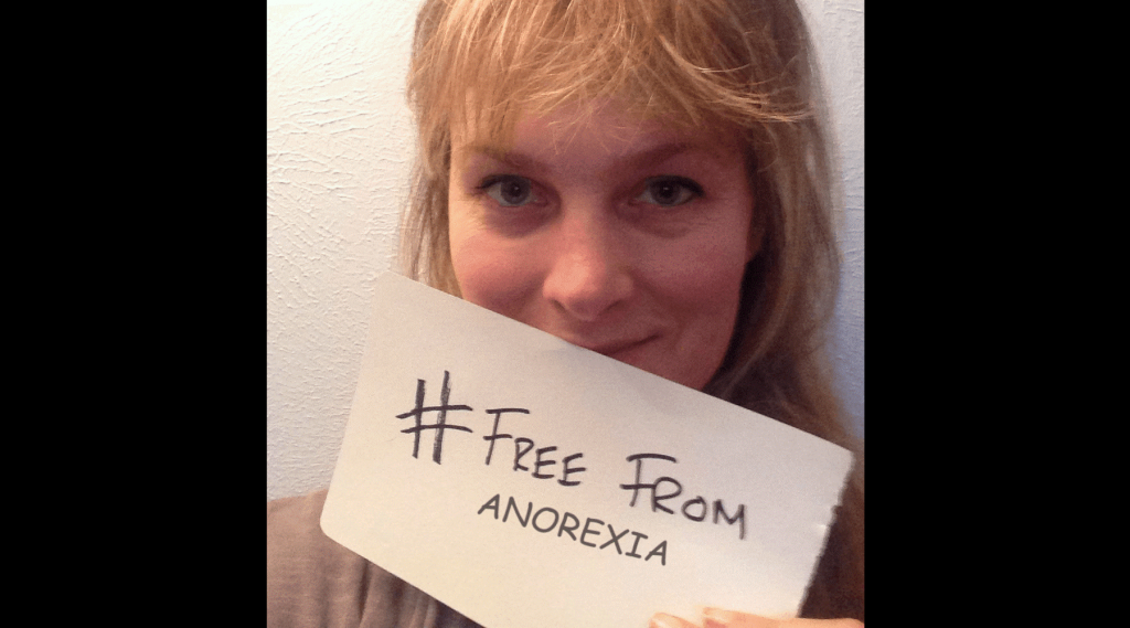 image showing a woman holding a sign saying free from anorexia