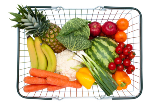 Steel wire shopping basket full of healthy food, on white background, cut out