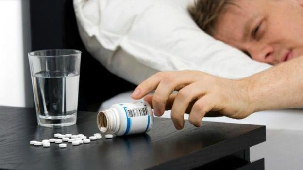 image showing a man reaching for sleeping pills